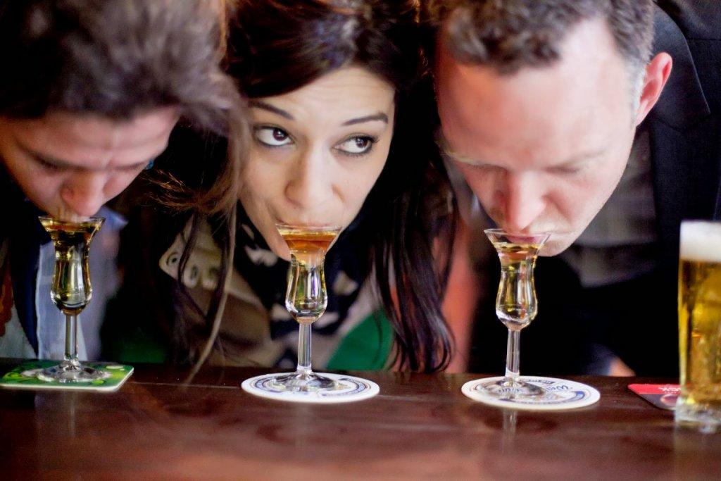 Dois homens e uma mulher bebendo jenever