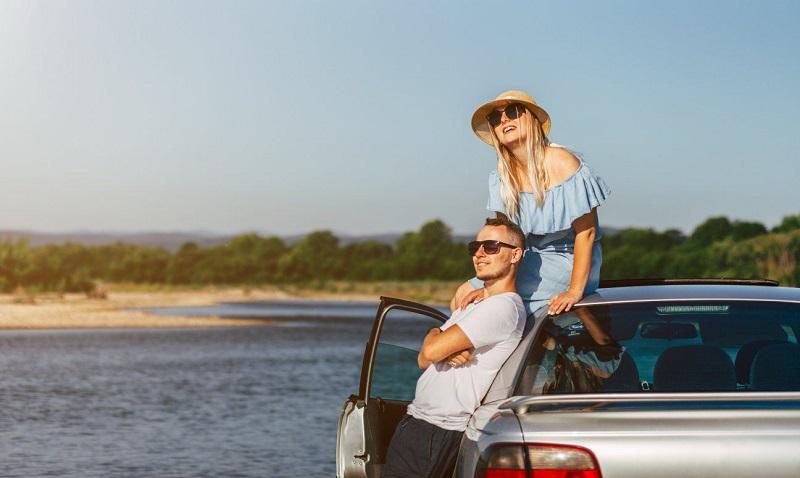 Casal em carro com paisagem de fundo