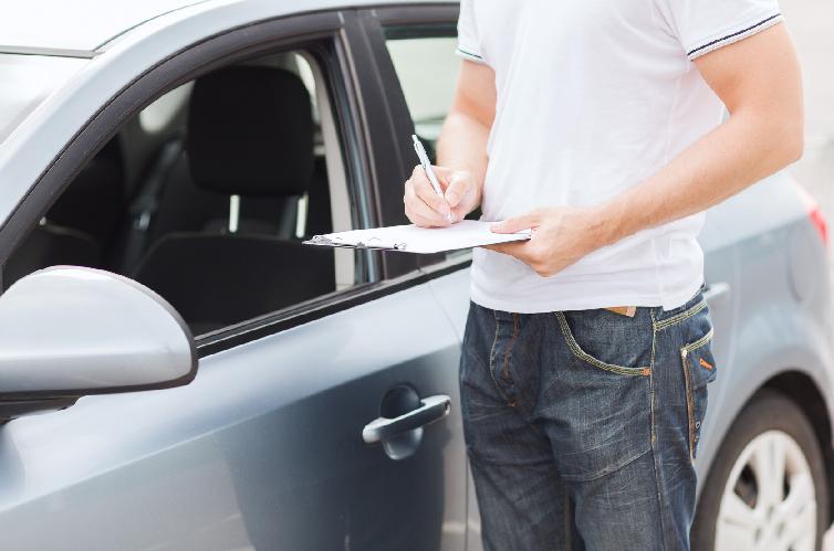 Homem ao lado de carro fazendo anotações